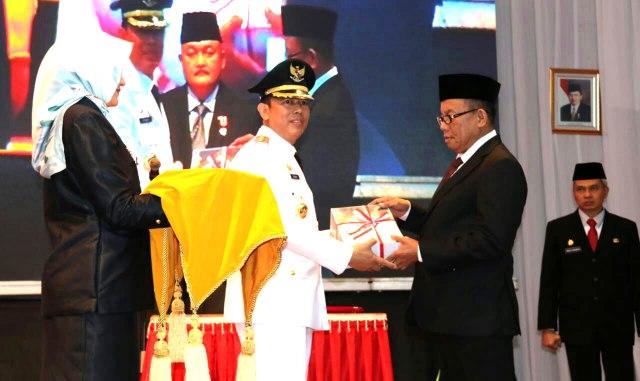 Mantan Bupati Muara Enim Ir H Muzakir Sai Sohar menyerahkan satu bundel buku mengenai program dan prestasi Kabupaten Muaraenim