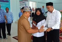 Teuku Irfan TB, Bupati Aceh Jaya, (kiri) menyerahan SK CPNS, secara simbolis.di Aula Kantor BPMPKB, Senin (18/3/2019).