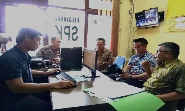 Kabag Hukum Pemkab Banyuasin DP Siregar SH (kanan) didampingi Kadis Pertanian Ir Babul Ibrahim (kiri ujung) saat menyiapkan laporan Bupati Banyuasin SA Supriono diruang SPKT Polres Banyuasin, Jumat (13/04/18)