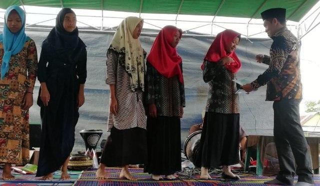 Darul Qutni (paling kanan) memberikan hadiah kepada santri TPA Dalwa Desa Purwosari Tanjung lago Kamis (14/03/19)