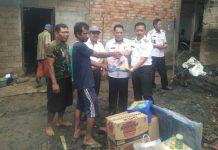 Kepala BPBD Banyuasin menyerahkan bantuan kepada warga Bukit dengan didampingi Camat Betung